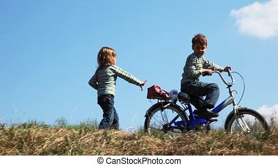 girl runs for the boy on bicycle on spring field