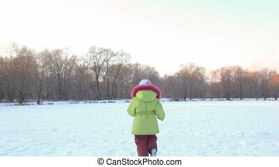 girl runs from camera in wintry snowfield, and comes back -...