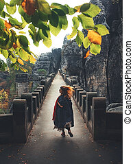 Girl runs on a large stone bridge between the rocks in autumn