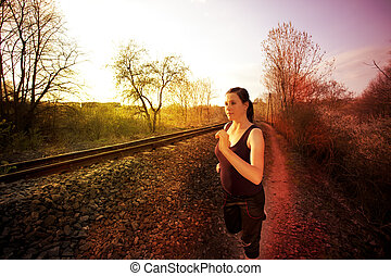 Girl runs on the road along the tracks and the sunset