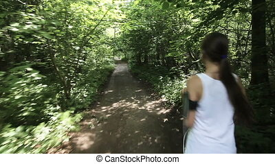Girl runs on the road in a field.