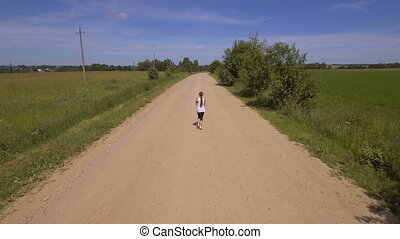 Girl runs on the road in a field.Aerial view.