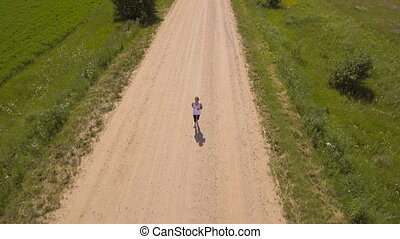 Girl runs on the road in a field.Aerial view. - Beautiful...