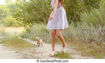 Girl runs with a puppy on the road.