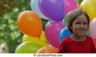 girl runs with multicolored balloons, Slow motion. Close up