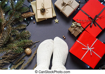 Girl s feet in socks, gift boxes, natural packaging materials, ribbon , branches, pine cone, led garland