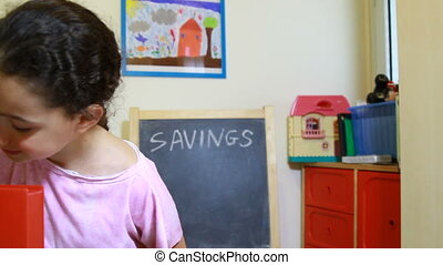 penny bank or money box - Girl save by putting money in...