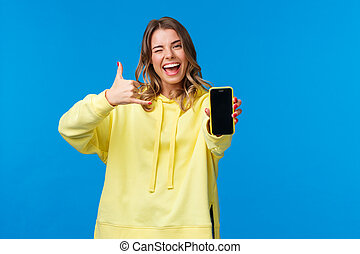 Girl say hit me up as trying get hot guy number, holding smartphone, showing mobile phone display, wink and make phone gesture, ask give her call, standing blue background