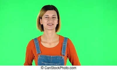 Girl says wow, waves his head approvingly and shows thumb like sign. Brown-eyed girl with an earring in her ear dressed an orange sweater and denim overalls on a green screen in the studio