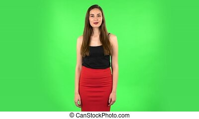Girl says wow with smile. Beautiful brunette with long hair, a gentle makeup in a black tank top and red skirt on a green screen in the studio