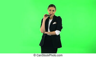 Girl says wow with smile. Girl with dark hair and glasses wearing a black business suit at green screen at studio.