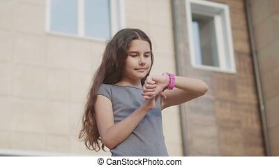 girl schoolgirl looking slow motion video at smart watch waiting for class to start lessons. little girl teenager internet social network on smart clock. school education concepts lifestyle