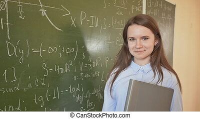 Girl schoolgirl posing against the backdrop of a school board painted in mathematical formulas.