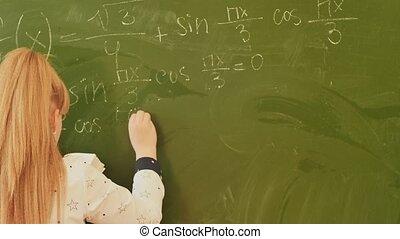 Girl schoolgirl writes on the blackboard mathematical formulas.