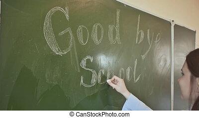 Girl schoolgirl writes on the blackboard phrase - Good bye school. Farewell to the school.