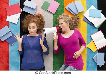 Girl screaming at her friend with loudspeaker