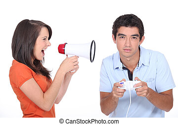 Girl screaming into megaphone whilst boyfriend plays video games