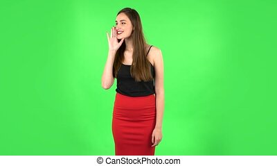 Girl screams calling someone on a green screen at studio