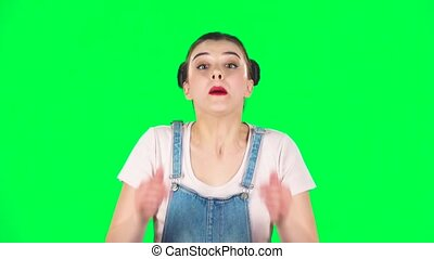 Girl screams calling someone on a green screen at studio, slow motion