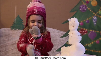 Girl sculpts a snowman in winter. Emotional portrait of cute little girl in winter. background of a painted Christmas tree and snow