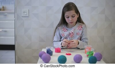Girl sculpts clay figure flower