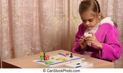 Girl sculpts crafts from plasticine sitting at a table on...