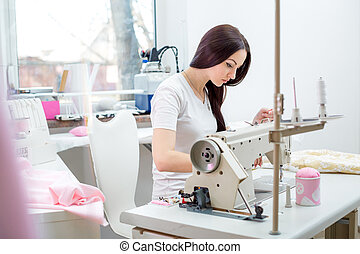girl seamstress sew on the sewing machine - beautiful woman...