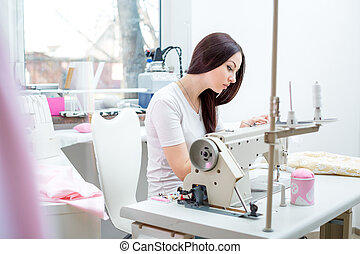 girl seamstress sew on the sewing machine - beautiful woman ...