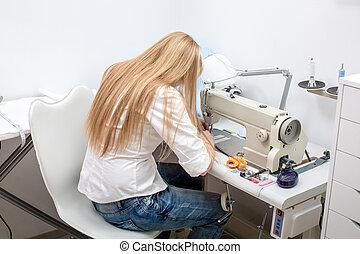 girl seamstress sew on the sewing machine