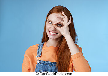 Girl search perfection. Charming pretty glad redhead female student assuring everything ok showing okay sign eye look through smiling delighted express positive attitude, blue background
