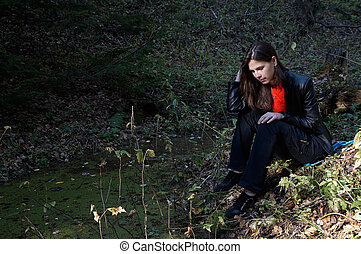 Girl seating near pond