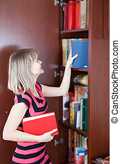 girl selecting book in bookcase