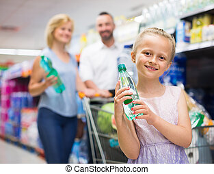 Girl selecting non-alcoholic beverage in plastic bottle in food store