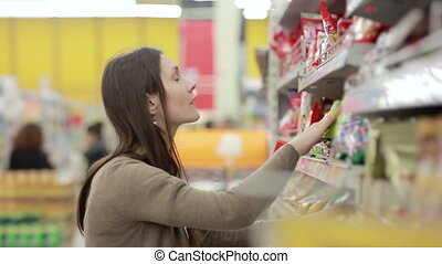 Girl selects the candy on the shelves in the store