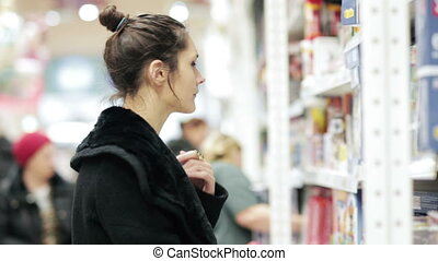 Girl selects the item on the shelves in the supermarket