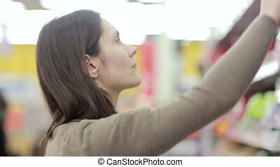 Girl selects the item on the shelves in the store