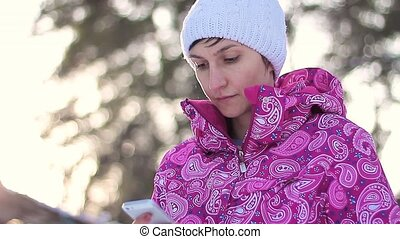 Girl send sms in winter forest