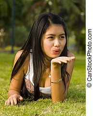 attractive asian girl out in the green sending a kiss