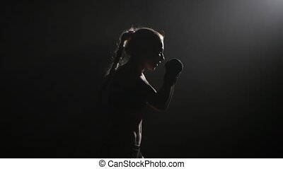 Girl sends a boxer hitting opponent. Silhouette. Black background . Side view. Close up