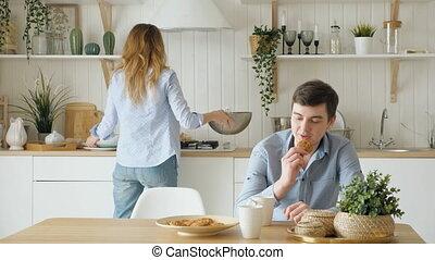 girl serves breakfast putting dumplings on plate kisses guy...