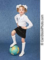 Girl set foot on globe like a soccer ball
