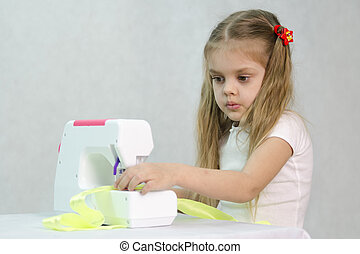 Girl sewing on the sewing machine