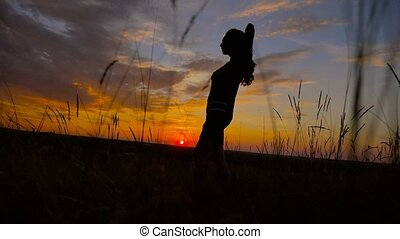 girl sexy beautiful her arms standing in a field at sunset slow motion video