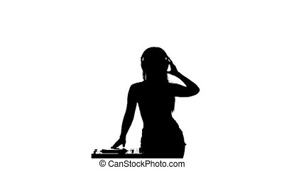 Girl sexy DJ turntable rotates while dancing. Slow motion. Silhouette