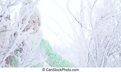 Girl shakes the snow from the tree branch in the forest. Happy childhood. Winter fun