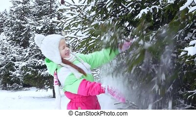 Girl shakes the snow from the tree branch in the forest....