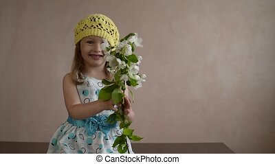 Girl shaking a blooming apple twig