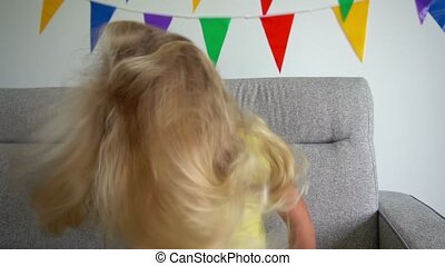 Portrait of pretty girl shaking head so blond hair is fluttering and looking in the camera smiling. Face of adorable child closeup. Gimbal slow motion shot.