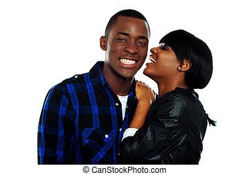 Girl sharing secrets with her boyfriend against white...