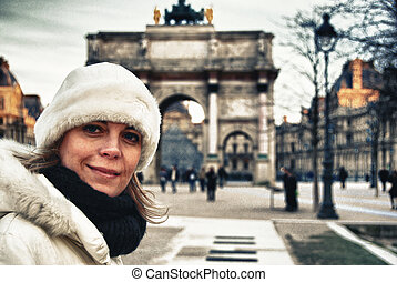 Girl shivering with the background of the Arc de Triomphe